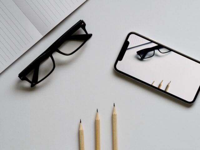 eyeglasses; silver iPhone X; three pencils; notebook flat lay photography